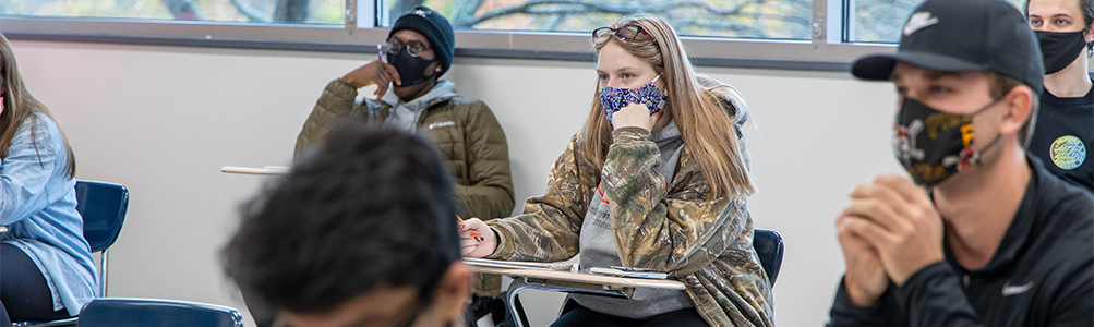 Students wearing masks sit in desks in a classroom
