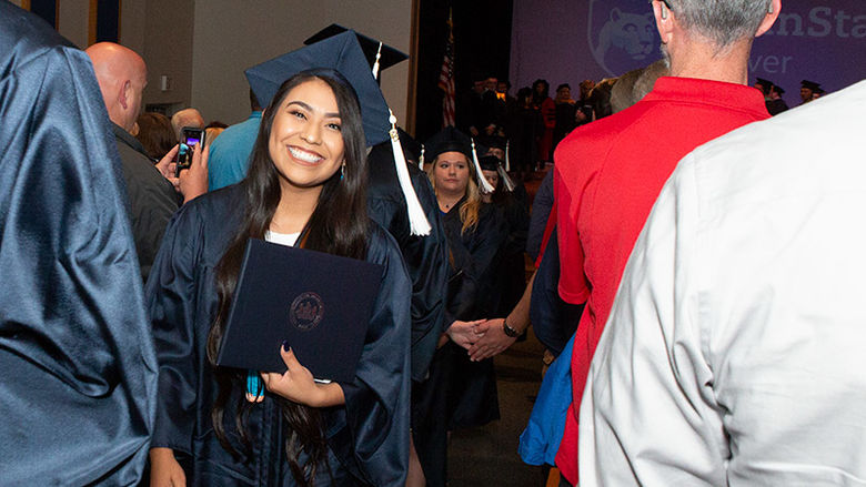 Ryanne Kie, bachelor of science in Psychology, exits the auditorium after commencement.