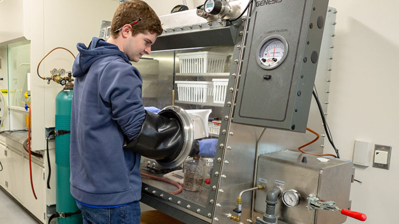 A student is working in front of a glass box. Rubber gloves, that are built into the box, extend up to his elbows as he reaches into the chamber.