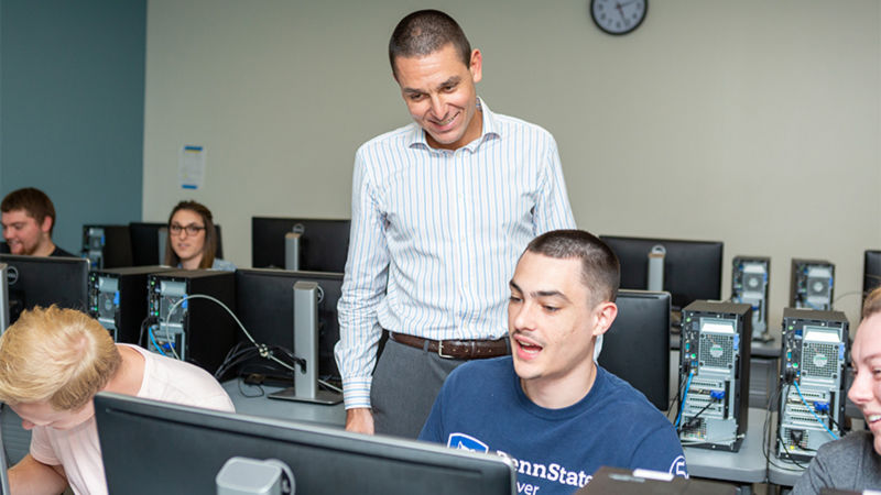 The professor, wearing a white dress shirt with blue vertical stripes, stands smiling behind a student seated at a computer.