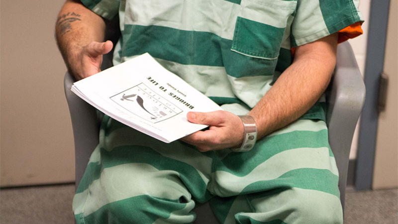 An inmate dressed in a prison jumpsuit holds a book that says Bridges to Life on the cover.