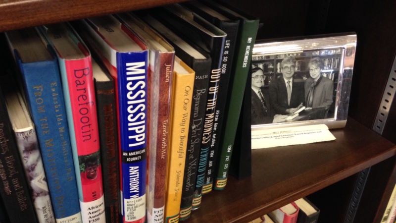 A photo of Russ Brignano sits beside books on a shelf.