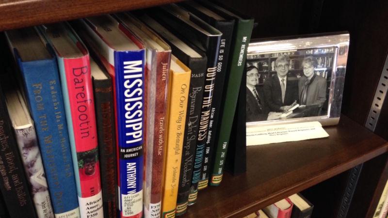 A photo of Russ Brignano sits beside books on a shelf.
