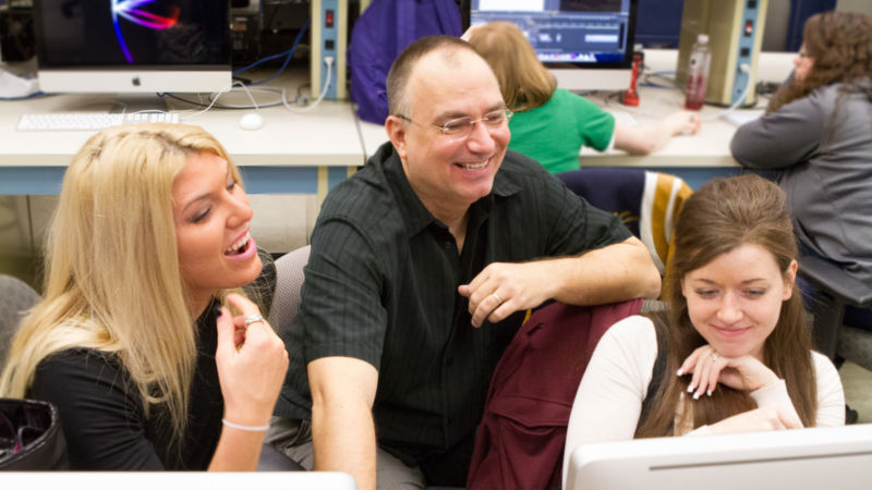 John Chapin and two students look at a computer screen.