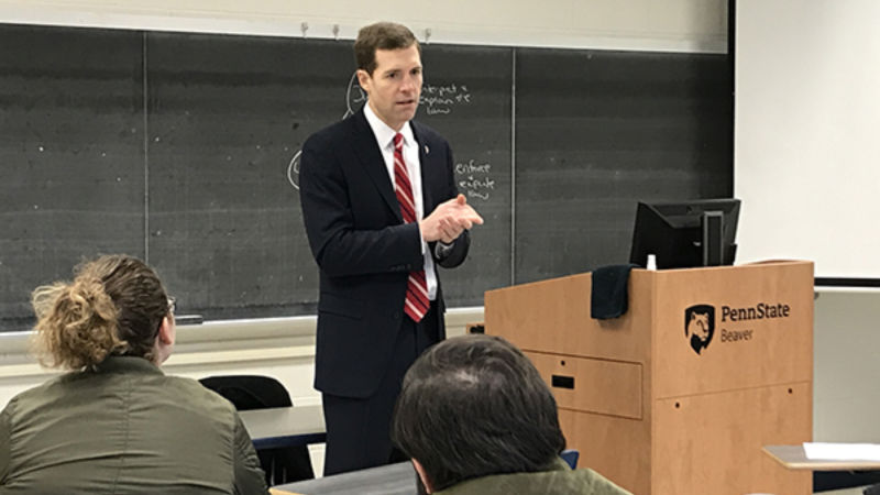 Conor Lamb, wearing a dark blue suit, stands in front of a class of students.