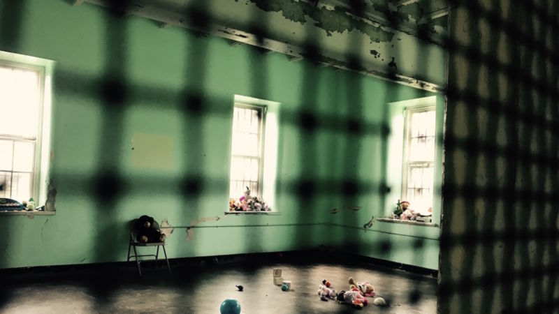 View, through caged door, of a nearly empty room in a former mental hospital.