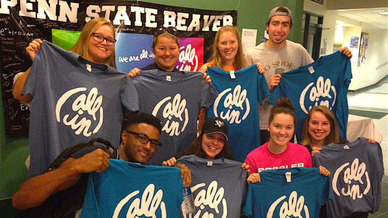 """Eight Beaver students pose with their """"All In"""" T-shirts in the Bistro."""