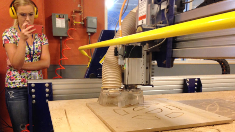Engineering student Leah Berry records the ShopBot in action with her smart phone.
