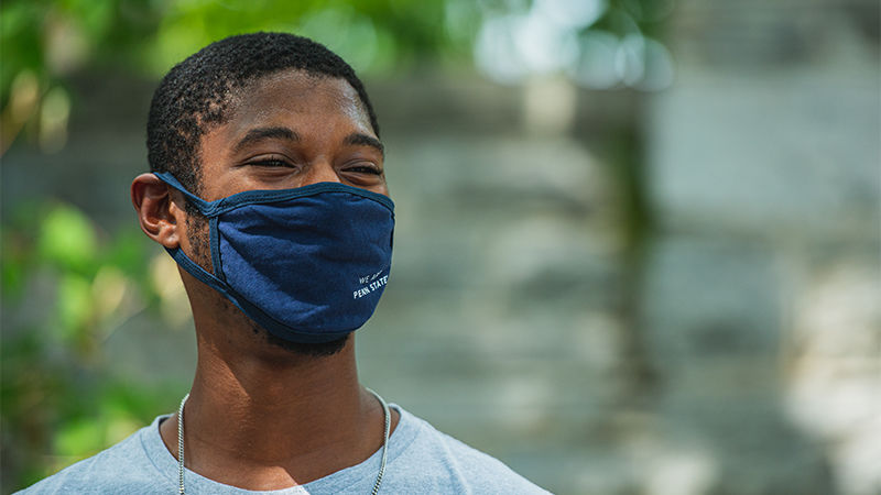 A young man wears a Penn State University face mask