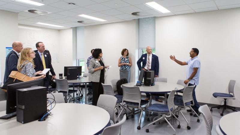 Instructor Ashu Kumar shows an IST classroom to a tour group.