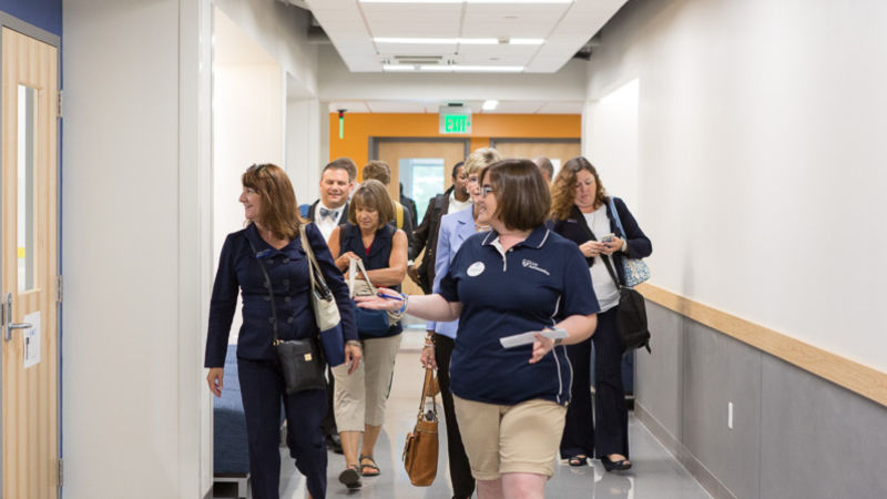A Lion Ambassador leads a group of alumni through the Michael Baker hallway.