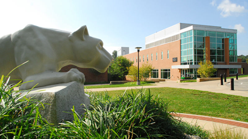 A Nittany Lion statue looms in the left foreground of the photo while the Ross Administration building can be seen in the background on a sunny day.