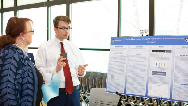 A male student wearing a white dress shirt and red tie explains his research to a professor in front of a poster board.