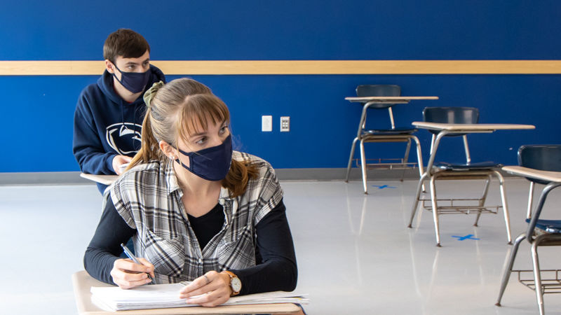 Two students wearing masks take notes in a classroom.