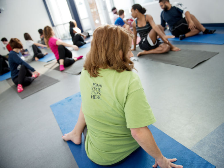A yoga instructor wearing a Penn State Lives Here shirt demonstrates a move to her class.