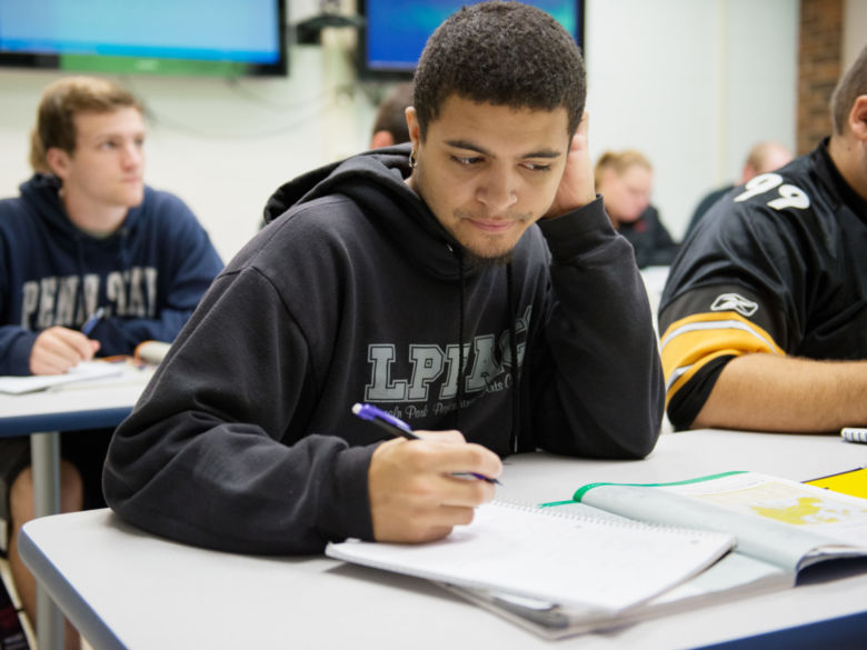 A student works in his textbook while in class.