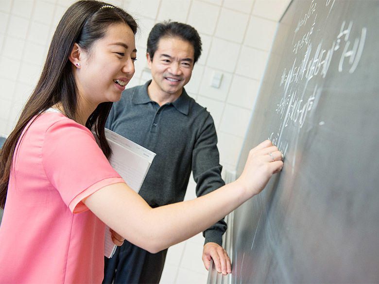 A student from China gets help from a professor on a math problem.
