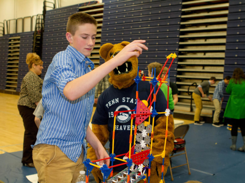 The Lion gives encouragement to a boy building a contraption with K'Nex at the Penn State Beaver STEM Challenge.