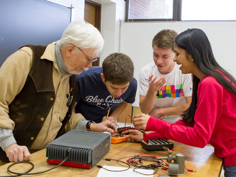 Physics professor Leo Takahashi works with students on an electrical engineering project.