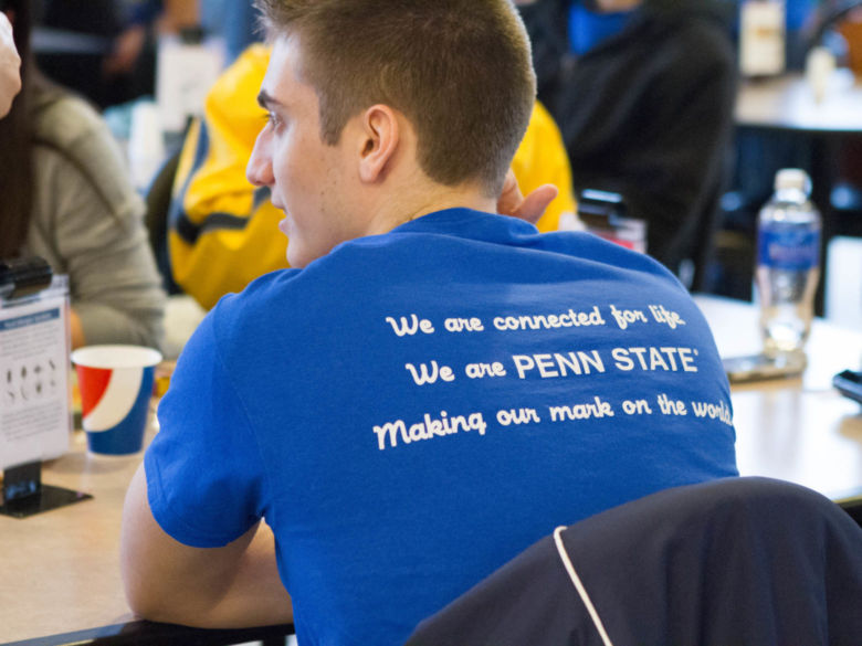 A student at a community service event wears a shirt that says we are connected for life; we are penn state, making our mark on the world.