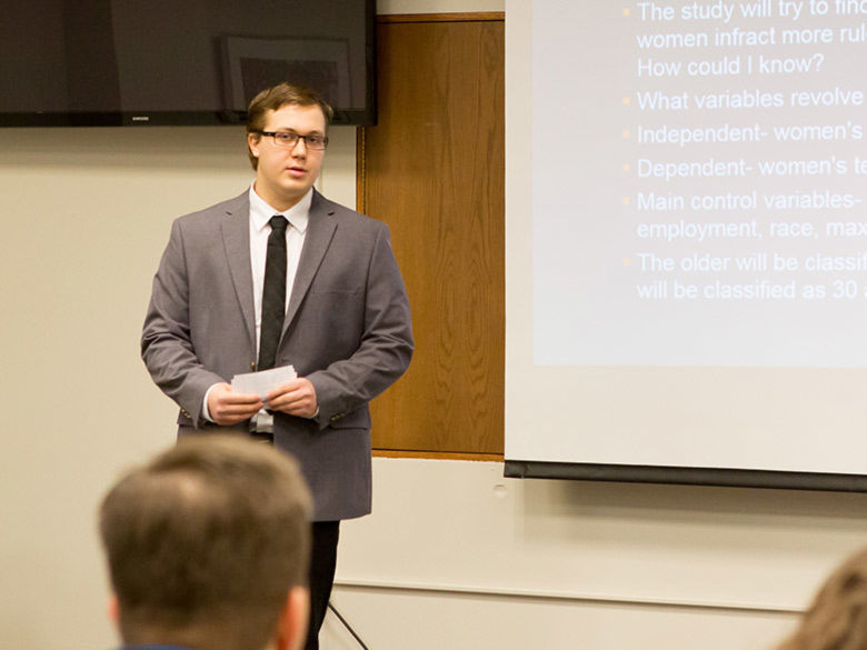 A male student wearing a suit gives a presentation
