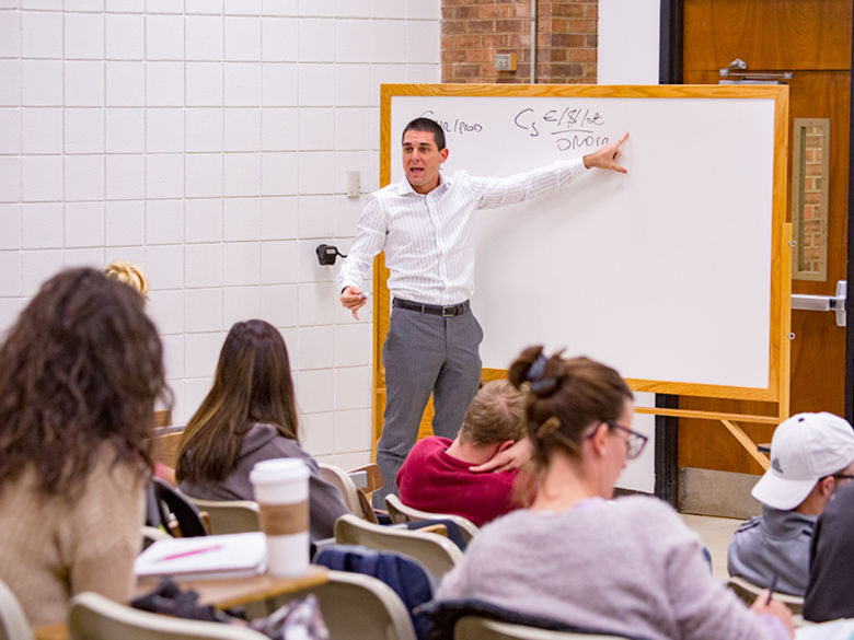 A professor lectures in front of a white board.
