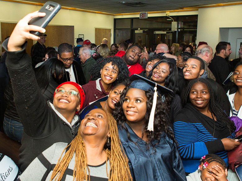 A large family takes a selfie with a Penn State Beaver graduate