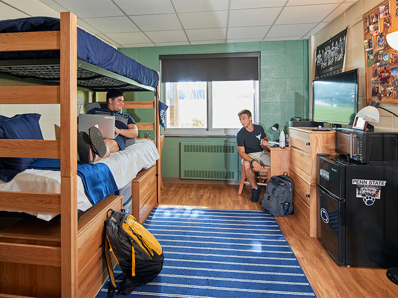 Two male students talk in a residence hall room. One is on a bunk bed, the other is at a desk.