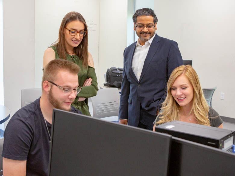 Three students work with Professor Ashu Kumar in a classroom.