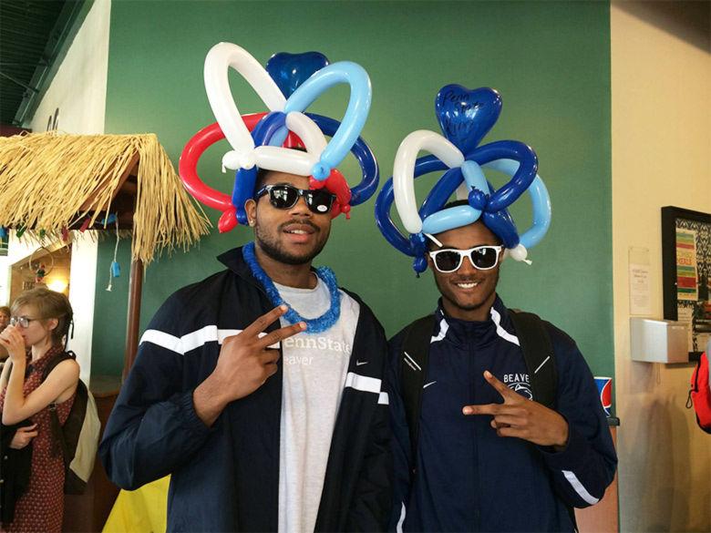 Two male students wear balloon animal hats