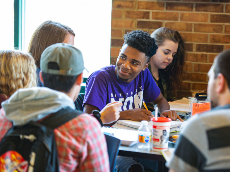 A group of students talk at a table in the Bistro.