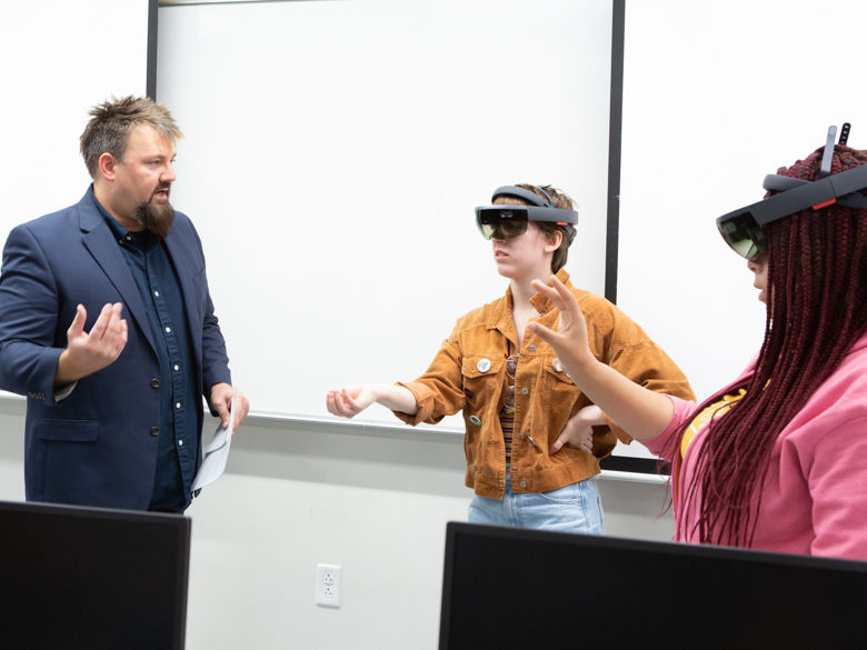Psychology professor Kevin Bennett works with two students learning about virtual reality equipment.