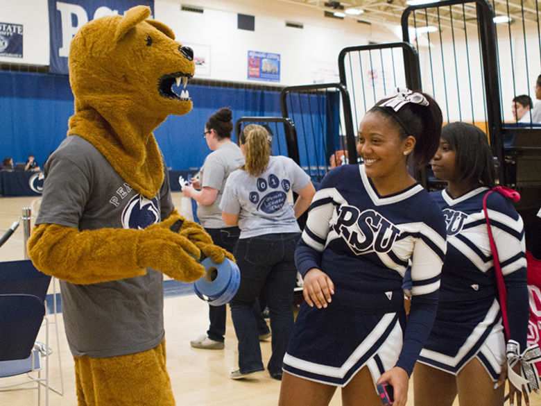 Cheerleaders hang out with the Nittany Lion at a basketball game