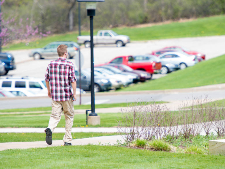 A male student walks past cars in one of the parking lots.