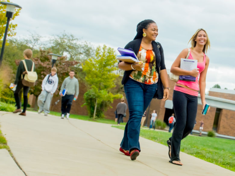 Two female students walk across campus