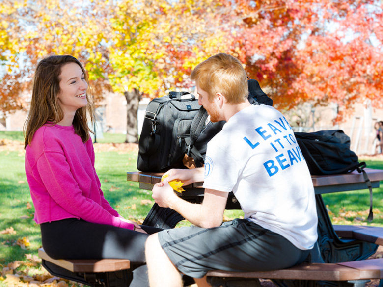 A female student and a male student sit and talk at a picnic table on campus.