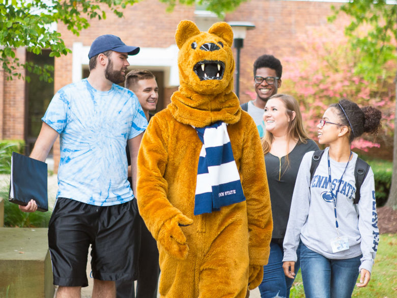 The Nittany Lion mascot walks away from the General Classroom Building with several students