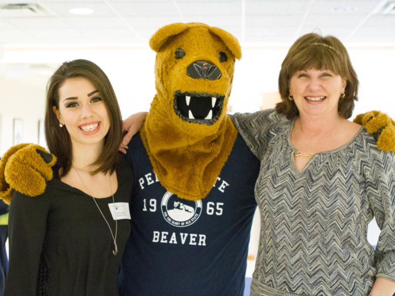 A student and her mother pose with the Nittany Lion at an accepted student event