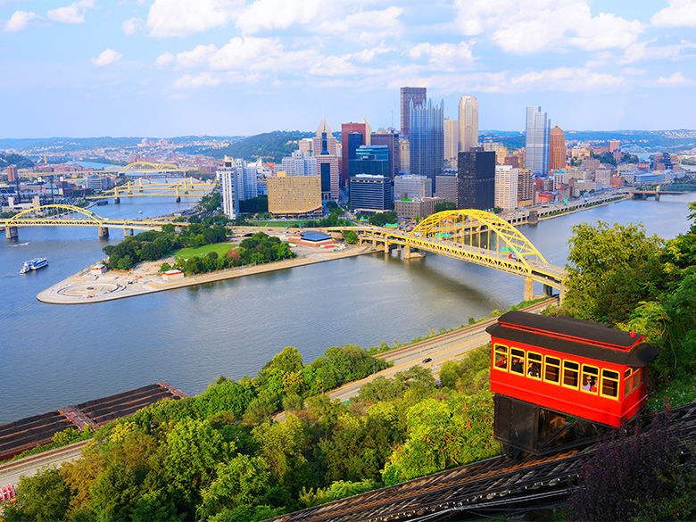 A trolley goes down the Duquesne Incline. In the distance is Pittsburgh's Golden Triangle.
