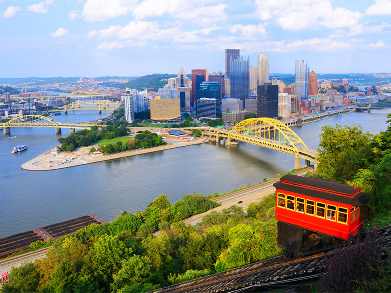 A trolley car goes down the Duquesne Incline. The Pittsburgh skyline is in the distance.