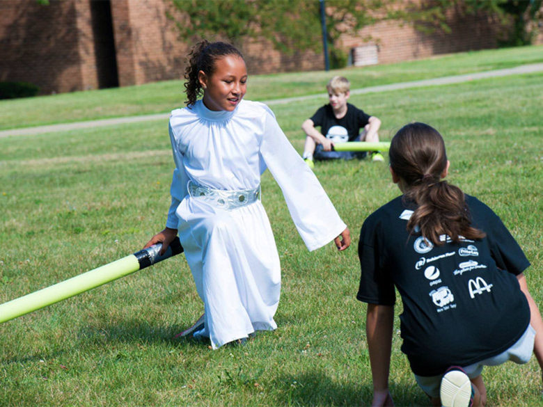A girl dressed as Princess Leia battles with a lightsaber at a youth camp.