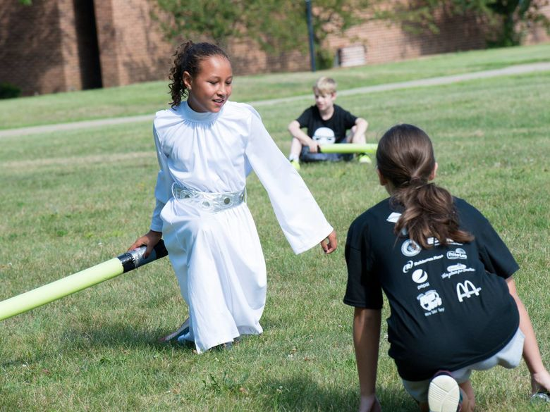 A girl dressed at Princess Leia has a light saber battle during a summer camp.