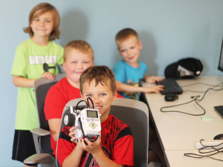 A group of four children show off a robot they made in Robotics Camp.
