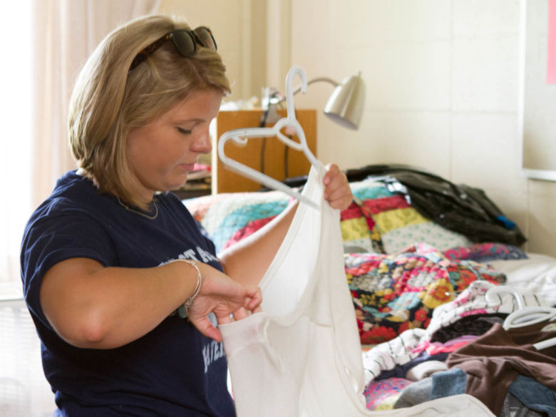 A female student hangs up her clothing at Harmony Hall after moving in to her room.