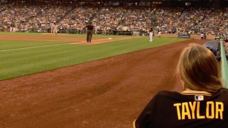 Taylor Myers watches baseball game from field level.