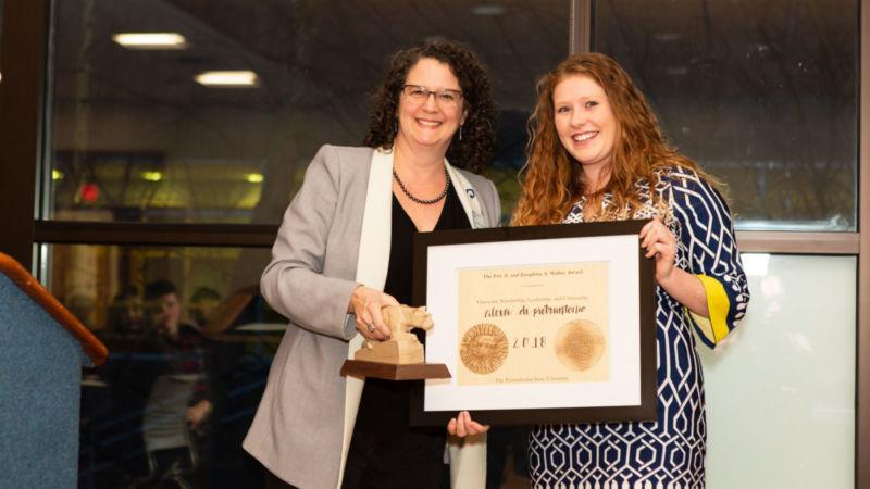 Chancellor Cushman hands Alexa Di Pietrantonio a framed certificate.