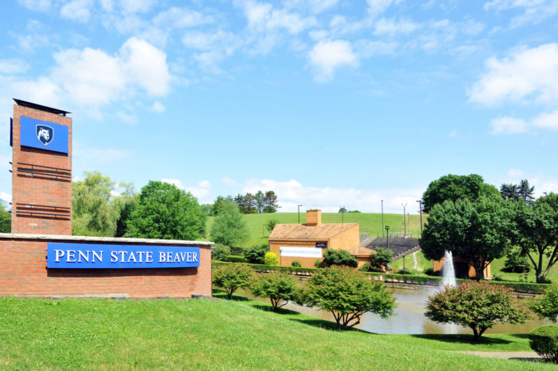 Campus entrance sign with pond and amphitheater in background.