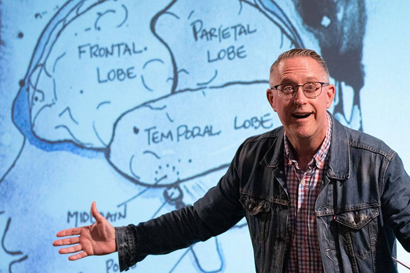 The professor gestures as he stands in front of the projected image of a hand-drawn brain.
