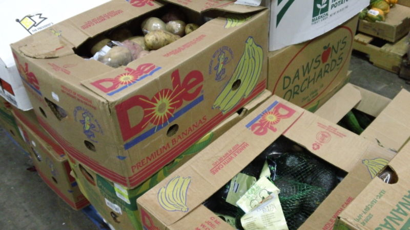 Boxes of food sit on the floor of the food bank warehouse.