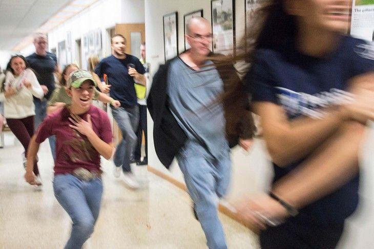 Student actors run down a hallway.